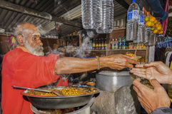 An old man with his daughter in a roadside stall. Kodaikanal, Inida - December 26, 2015: An old man with his daughter selling hot corn and masala chickpeas in a Stock Photo