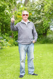 Old man on his grass lawn. Vertical thumbs up from a smiling happy senior old man on grass lawn, full body length Royalty Free Stock Photography