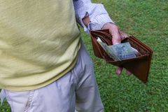 An old man with his wallet in the hand. An old man with his pocket book in his left hand royalty free stock image