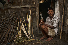 Old man with his wood. Portrait of old man sitting in front of his house with parang and wood indonesia stock photography