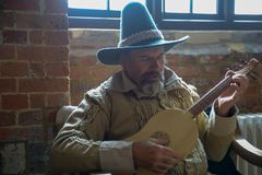Old man in historical costume playing lute royalty free stock images