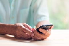 Old man hold black smartphone with left hand and touch screen with right fingers. On light brown wooden table surface Stock Photography