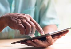 Old man hold tablet with left hand and touch screen with right index finger. On light brown wooden table surface royalty free stock photography