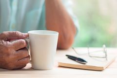 Old man hold white cup of tea or coffee with right hand on light brown wooden table surface Stock Photo