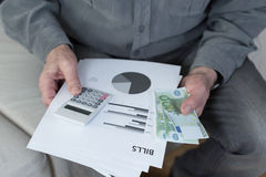 Old man holding bills Stock Image
