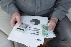 Old man holding bills Stock Image