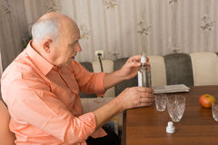 Old Man Holding a Bottle of Wine on the Table. Close up Side View of a Serious Old Man Holding a Bottle of Vodka Wine on the Wooden Table Royalty Free Stock Photo