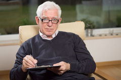 Old man holding clipboard Stock Photo