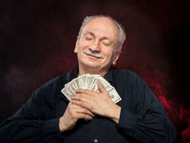 Old man holding dollar bills. Lucky, old man holding with pleasure group of dollar bills Stock Photography