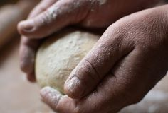 Old man holding a dough. Cook preparing raw dough for pizza. Handmade Stock Photography