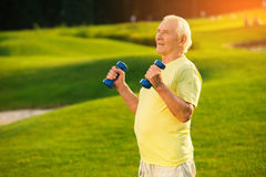 Old man holding dumbbells. Person on nature background. Training program for retired athletes. Don't lose self esteem Stock Image