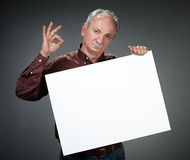 Old man holding empty bill board Stock Image