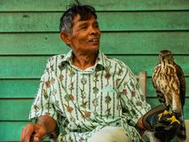 Old man holding a falcon on his arm at Sam Pan Nam floating mark stock photos