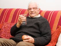 Old man holding glass water Stock Photos