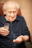 Old man holding a glass of water and pills Royalty Free Stock Photos