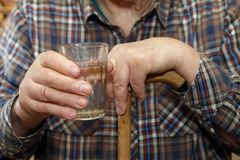 Old man holding a glass of water Stock Photos