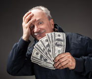 Old man holding group of dollar bills. Lucky old man holding with pleasure group of dollar bills. Focus on money Stock Photography