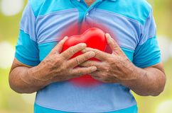 Old man holding heart because of heart infarction Stock Photo