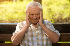 Old man holding his head. Elderly person has headache. Health is in danger. Discomfort grows into pain Stock Photography