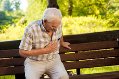 Old man holding his stomach. Senior male near park bench. Constant pain under ribs. Problems with health stock photography