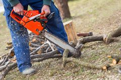 Old man holding orange chainsaw with his bare hands and cutting a branch placed on the ground. Orange chainsaw in action.  royalty free stock photo