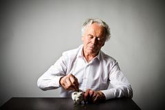 Old man holding piggy bank. Senior man holding piggy bank. Financial security planning concept Royalty Free Stock Photography