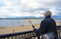 Old man holding vintage umbrella looking far. On the river beach outdoors sky background. Back side view of traveller explorer. Tourist senior Stock Photography