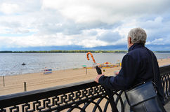 Old man holding vintage umbrella looking far. On the river beach outdoors sky background. Back side view of traveller explorer. Tourist senior Stock Images