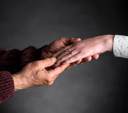 Old man holding young woman's hand. On a gray background royalty free stock photos