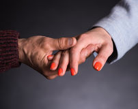 Old man holding young woman's hand. On a gray background royalty free stock photo
