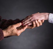 Old man holding young woman's hand. On a gray background stock photos