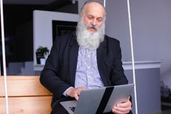 Old retired man uses laptop and communicates with colleagues beh royalty free stock photos