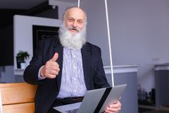 Old retired man uses laptop and communicates with colleagues beh stock photography