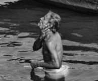 Old man in holy river Ganga taking bath. stock photos