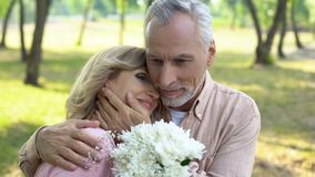 Old man hugging happy wife holding flowers, celebrating marriage anniversary. Stock photo royalty free stock images
