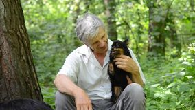 Old man and dog in the forest. Old man hugging his dog while sitting in the woods in the summer. Portrait of an elderly man with a dog on the background of trees stock video footage