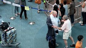Old man hugging his friend at international arrival lobby stock video