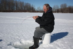 Old man ice fishing 3. A man ice fishing for trout on a frozen lake Royalty Free Stock Photo