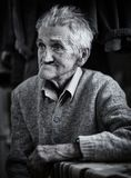 Old man indoor, monochrome toned royalty free stock photography