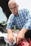 Old man installs tail light on vehicle Royalty Free Stock Photography