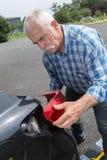 Old man installs tail light on vehicle Stock Photos