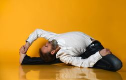 Old man practicing yoga doing stretching exercises against orange background stock photo
