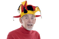 Old man in a jester's hat. Funny old man in a traditional jester's hat. White background royalty free stock photo
