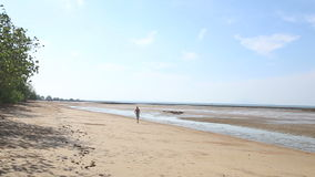 Old man jogs along beach at low tide stock footage