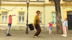 Old man rope skipping with three girls. Old man jumping on a skipping rope with three girls in the street stock video footage