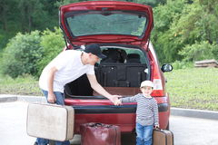 Old man and kid loads his red car suitcases Stock Image