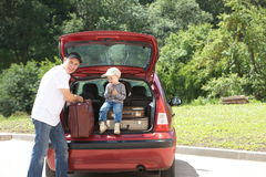 Old man and kid loads his red car suitcases Stock Photography