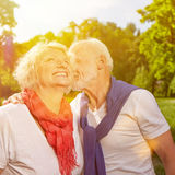 Old man kissing senior woman on cheek. Old men kissing happy senior women on cheek in summer Stock Photos