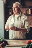 Old man in kitchen stock photo