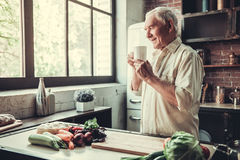Old man in kitchen. Handsome senior man is holding a cup, smelling aroma and smiling while standing in kitchen Royalty Free Stock Photo